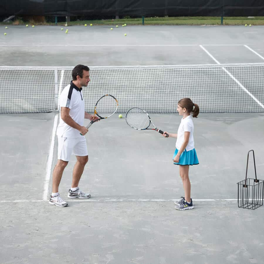 Father and daughter playing tennis